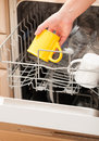 Hand putting a mug into a dishwasher yellow Royalty Free Stock Image