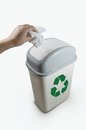 Hand putting a paper garbage into recycling bin on white background Royalty Free Stock Image