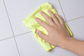 Hand with rag cleaning tile wall yellow Royalty Free Stock Image