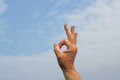 Hand raised with the ok sign a doing or yes a blue sky background Stock Photography