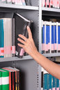 Hand reaching for book on a shelf Royalty Free Stock Photos