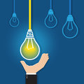 Hand reaching for a  glowing unique light bulb Royalty Free Stock Photo