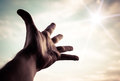 Hand reaching to towards sky of a man color toned image Royalty Free Stock Photography