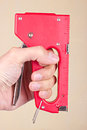 Hand with red industrial stapler on beige background Royalty Free Stock Photo