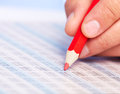 Hand with a red pencil finance and accounting business background Royalty Free Stock Images