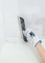 Hand repairs gypsum plasterboard frame with spackling paste Royalty Free Stock Image
