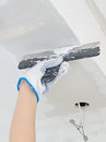 Hand repairs gypsum plasterboard frame with spackling paste Stock Image