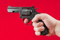 Hand with revolver a on a red background Royalty Free Stock Image