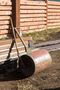 Hand roller and rake lying on bare ground the Royalty Free Stock Image