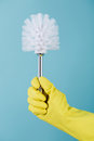 Hand in rubber yellow glove holds brush for toilet on blue background. cleaning. Royalty Free Stock Photo