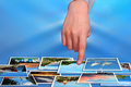 Hand selecting summer holidays photos on digital display Stock Photo