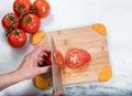 Hand slicing fresh garden tomato on natural bamboo cutting board Royalty Free Stock Photo