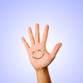 Hand with smiley palm face icon on blue background Stock Photography