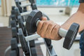 Hand of sport man is holding dumbbell, exercising working out at the fitness Royalty Free Stock Photo