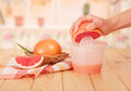 Hand squeezes fresh grapefruit juice in the kitchen Royalty Free Stock Photography