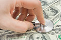 Hand with stethoscope and money Royalty Free Stock Photo