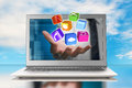 Hand stretch out laptop screen with app blocks and sky background Royalty Free Stock Photography