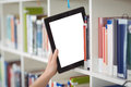 Hand of student keeping digital tablet in bookshelf in library Royalty Free Stock Photo