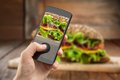 Hand taking photo of sandwich with smatphone Royalty Free Stock Photo