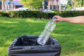 Hand throwing empty plastic bottle into the trash Royalty Free Stock Photo