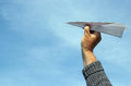 Hand throwing a paper airplane or dart holding about to throw it into the blue sky Royalty Free Stock Photos