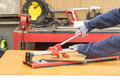 Hand tile cutter worker cutting with Stock Image