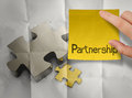 Hand touch sticky note partnership puzzle with crumpled recycle paper background as concept Royalty Free Stock Images