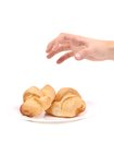 Hand trying to grab croissants isolated on a white background Stock Photo