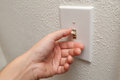Hand turning wall light switch off Royalty Free Stock Photo