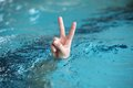 Hand with two fingers up in the victory or peace symbol above water body language surface Royalty Free Stock Photography