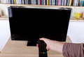 Hand using remote control turning off the TV Royalty Free Stock Photo