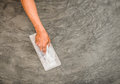 Hand using steel trowel to finish polished wet concrete surface close up of floor of Royalty Free Stock Image