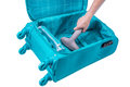 Hand vacuum cleans suitcase turquoise with the gray cleaner Stock Photography