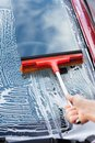 Hand washing car window with mop Royalty Free Stock Photo