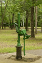 Hand water pump antique green operated among the trees Stock Photography