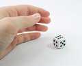 Hand with white dice over a plain gray background Royalty Free Stock Photo