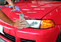 Hand with a wipe the car polishing on red Royalty Free Stock Image
