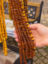 Hand of woman with shiny womanly amber necklaces on stall at the bazaar Royalty Free Stock Photo