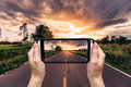 Hand woman taking photo at road and sunset. Royalty Free Stock Photo