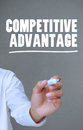 Hand writing competitive advantage with a marker on grey background Royalty Free Stock Photos