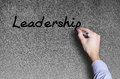Hand writing a leadership word written on blackboard by Royalty Free Stock Image