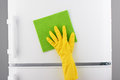 Hand in yellow glove cleaning white refrigerator with green rag Royalty Free Stock Photo