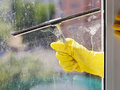 Hand in yellow glove cleans window by squeegee Royalty Free Stock Photo