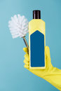 Hand in yellow glove holds bottle of liquid detergent for toilet and brush on blue background. Royalty Free Stock Photo