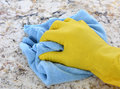 Hand in yellow latex glove with blue towel closeup of a a using a to clean a granite counter top Stock Photo