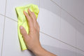 Hand with yellow rag cleaning the bathroom tiles male Stock Photo