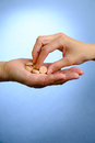 Hand of young woman and elderly woman holding the pills on blue background Stock Photos