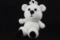 Handcrafted crochet teddy bear a small white crocheted on a black background Royalty Free Stock Photos