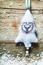Handcrafted embroidered christmas tree textile decoration with a reindeer and little bell hanging on a rustic textured wood Stock Photo