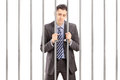 Handcuffed businessman in suit posing in jail and holding bars isolated on white background Stock Photography